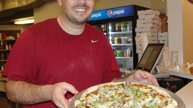 Owner Mike Mathew holds the signature Philly cheese steak pizza at Patriot Pizza located at 1146 Walnut St.