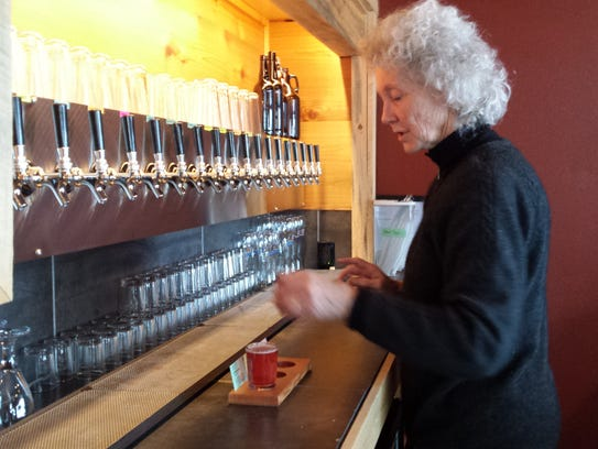 Sam Bailey, co-owner of Crush Cider Cafe, pours a sample