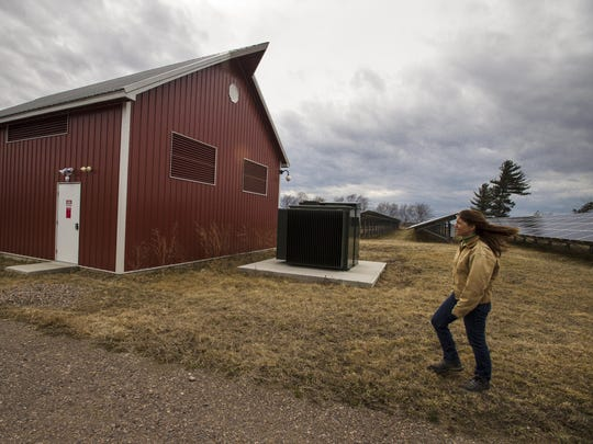 Meg Armstrong Whitcomb, a consulting engineer, approaches the transformer building at the eastern edge of the solar array on her family's farm in Essex Junction.