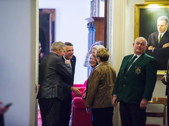 Gov. Phil Scott is greeted by a party of legislators in the doorway to his ceremonial office before delivering his budget address to the Legislature at the Statehouse in Montpelier on Tuesday, January 23, 2018.