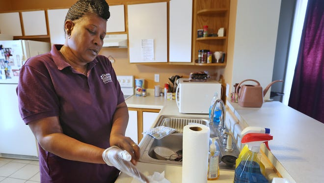 Kathy Young, an employee with Home Instead Senior Care, cleans her client's kitchen on March 18, 2015. Young used to earn about $60,000 a year working in collections for a Carmel banking company. However, she lost her job when the company closed in 2008 and now earns about $13,000 a year as a home health care worker.