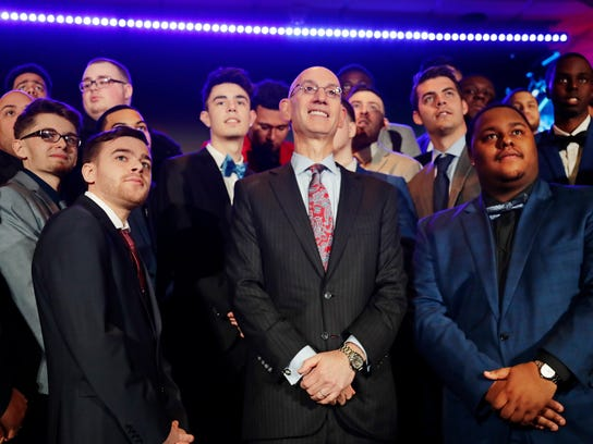 NBA Commissioner Adam Silver, center, poses for photographs with gamers at the NBA 2K League draft Wednesday, April 4, 2018, in New York. Launching in 2018, the league will feature the best NBA 2K players in the world and will draft players to compete as unique characters in 5-on-5 play against the other teams in a mix of regular-season games, tournaments and playoffs. (AP Photo/Frank Franklin II)