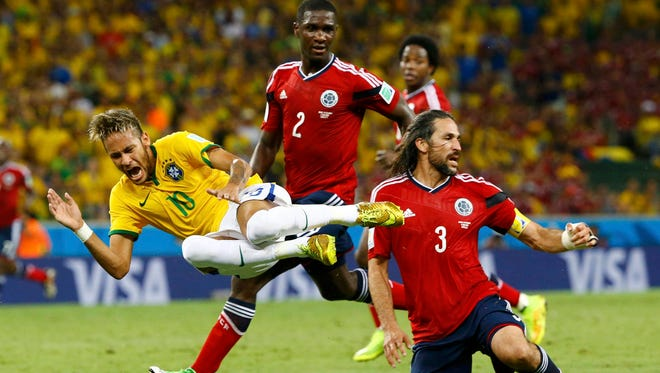 Brazil's Neymar is fouled by Colombia's Mario Yepes during their 2014 World Cup quarter-finals at the Castelao arena in Fortaleza July 4, 2014.