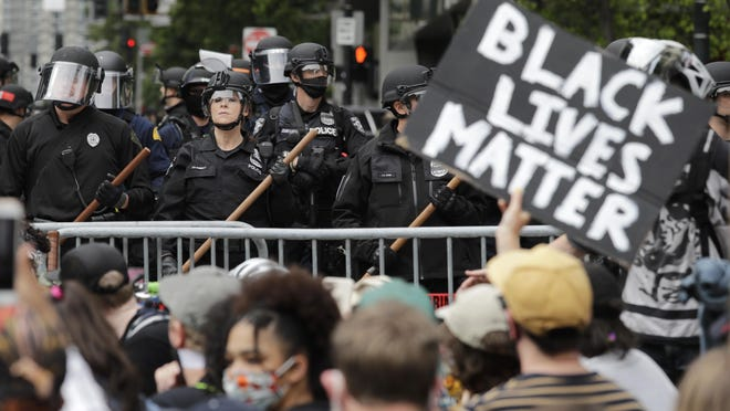 Police officers behind a barricade look on as protesters fill the street in front of Seattle's City Hall on June 3 following protests over the death of George Floyd.