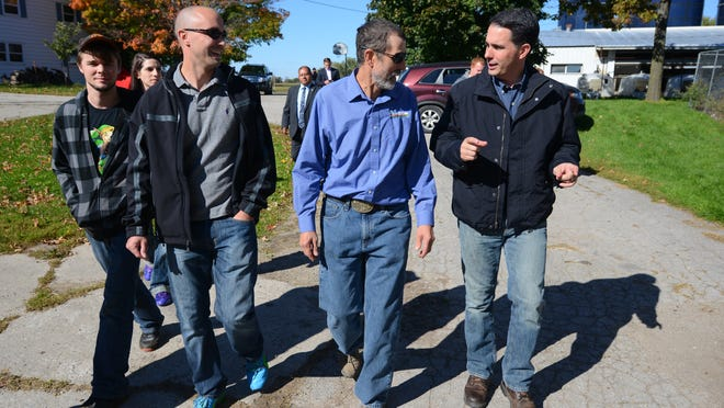 Gov. Scott Walker, right, tours Diederich Farm with owner Raymond Diederich, center, and his son Daniel on their De Pere dairy farm.