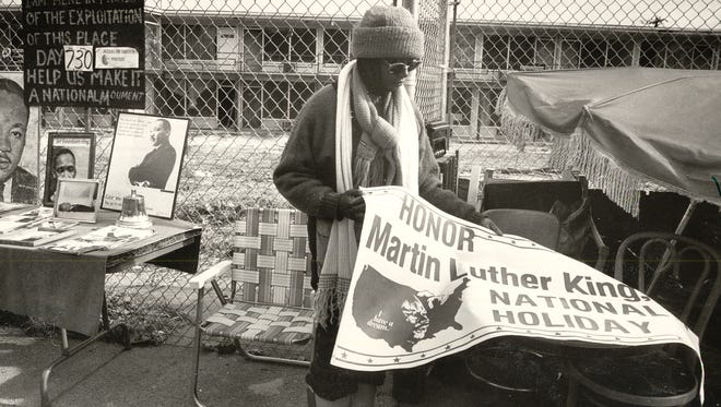 March 31, 2018 - Jacqueline Smith, prepares to hang a banner honoring the birthday of Dr. Martin Luther King Jr. in 1990. Smith has been encamped in protest on the sidewalk across from the Lorraine Motel since she was evicted in March 1988.