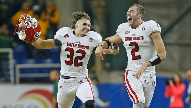University of South Dakota's Jet Morland (32) and quarterback Ryan Saeger celebrate their 24-21 win over NDSU in October. The Coyotes' winning ways this year has earned the respect of their rivals in Brookings.