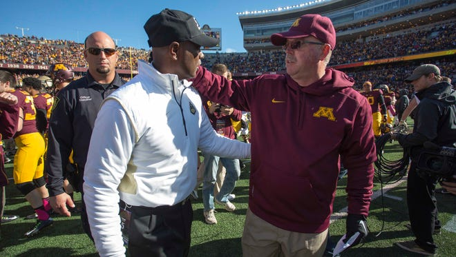 Purdue head coach Darrell Hazell and Minnesota head coach Jerry Kill shake hands after the game at TCF Bank Stadium.
