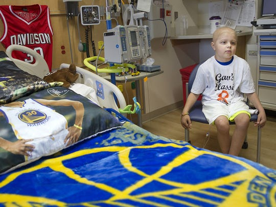 """At right, Brody Stephens, 7, sits by his Golden State Warriors-adorned bed topped with Stephen Curry pillows, at Riley Hospital for Children, Wednesday, July 13, 2016. Brody's advice for other kids who have been diagnosed with cancer? """"Fight."""""""