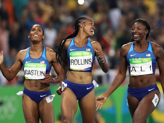 Gold medal winner Brianna Rollins, center, silver medal winner, Nia Ali, right, and bronze medal winner Kristi Castlin, all from the United States, pose with their country's flag after the 100-meter hurdles final,during the athletics competitions of the 2016 Summer Olympics at the Olympic stadium in Rio de Janeiro, Brazil, Wednesday, Aug. 17, 2016. (AP Photo/Lee Jin-man)