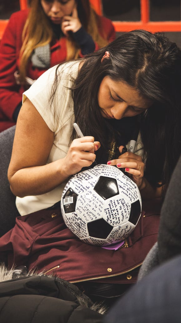 Erika Castillo, former high school classmate of Vicente Mundo, signs soccer ball in remembrance of him. (Walbert Castillo/USA TODAY College)