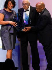 Journalist Simeon Booker, center, is presented with a Phoenix Award at the Congressional Black Caucus Foundation's annual Legislative Conference Phoenix Awards Dinner in Washington,  Saturday,  Sept. 18, 2010.