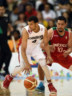Jamal Murray (L) of Canada moves the ball against Mexico during the Men's Basketball Preliminary Round at the 2015 Pan American Games in Toronto.