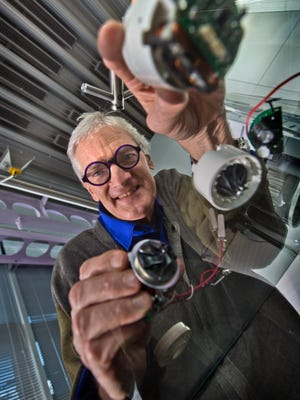 Dyson founder and chief engineer James Dyson shows off the digital motors the company's R&D arm developed.