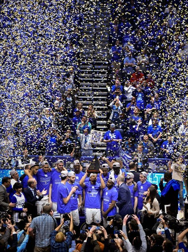 Kentucky guard Isaiah Briscoe (13) holds up the trophy after their SEC Men's Championship victory against Arkansas at Bridgestone Arena Sunday, March 12, 2017 in Nashville, Tenn.