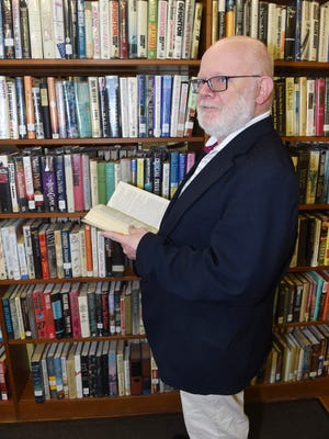 Greg Callahan, 64, director of the Hyde Park Free Library, peruses one of the bookshelves.