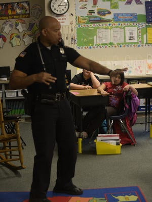 Officer Tim Davis shows his technique with his baton to third-graders at Starr Elementary School.