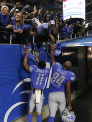Marvin Jones and Hakeem Valles hand sweat bands to Lions fans as they leave the field following the Lions' 35-11 win over the Packers, Sunday, Dec. 31, 2017 at Ford Field.