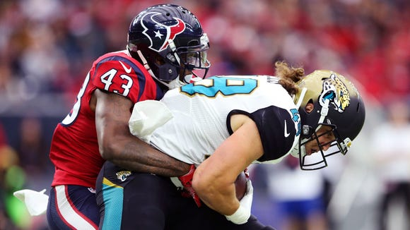 Houston Texans strong safety Corey Moore (43) tackles Jacksonville Jaguars tight end Alex Ellis (48) during the first quarter at NRG Stadium.