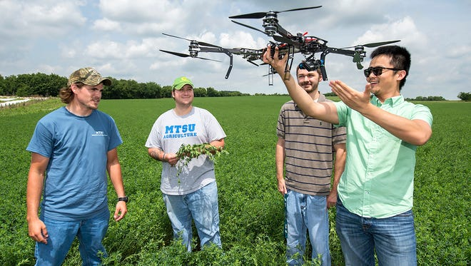 From left, senior Trevor Hasty, junior Daniel Troup and senior William West watch as MTSU School of Agribusiness and Agriscience professor Song Cui demonstrates unmanned aircraft systems.
