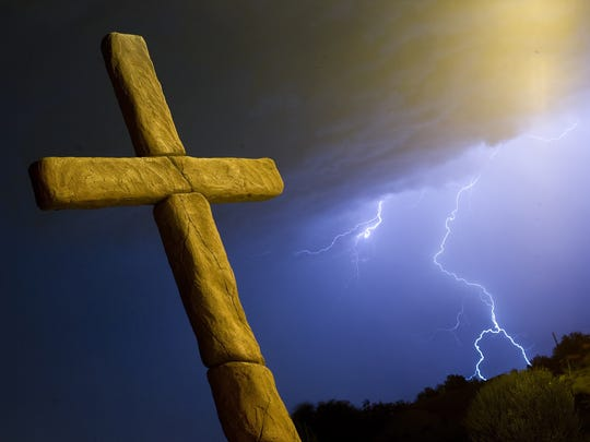 Lightning from a monsoon storm crackles behind a cross outside the West Valley Family Church.