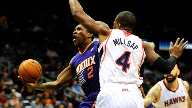 Mar 24, 2014; Phoenix Suns guard Eric Bledsoe (2) tries to reach the basket past Atlanta Hawks forward Paul Millsap (4) during the first half at Philips Arena.