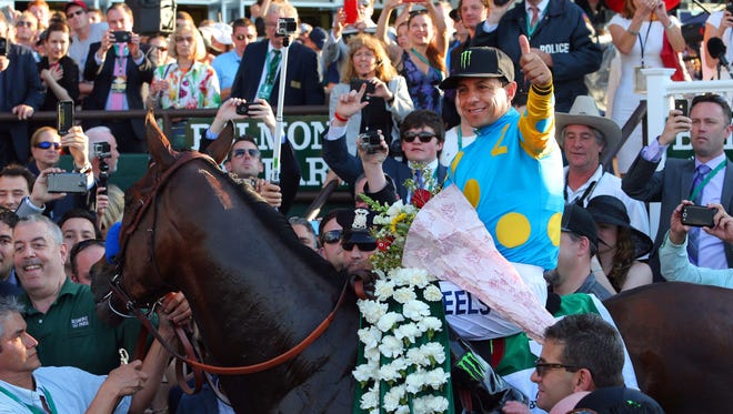American Pharoah jockey Victor Espinoza gives a thumbs up in the winner's circle after winning the 2015 Belmont Stakes, and racing's Triple Crown.