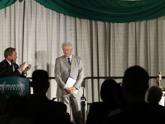 Former Michigan Governor James Blanchard, left, and guests applauds former President Bill Clinton Wednesday, Nov. 18, 2015, at the Kellogg Center in East Lansing after Clinton was presented with the inaugural Spartan Statesmanship Award for distinguished public service.