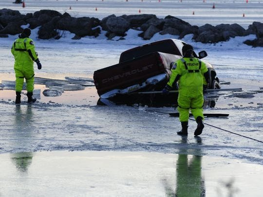 Clay Township firefighters approach a truck that had crashed through the ice on Lake St. Clair.