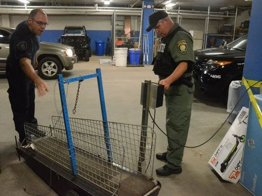 Andrew Olson, left, a Crime Laboratory Technician and Mike Ehart, Animal Control Officer, with a treadmill seized on Battle Creek Avenue.