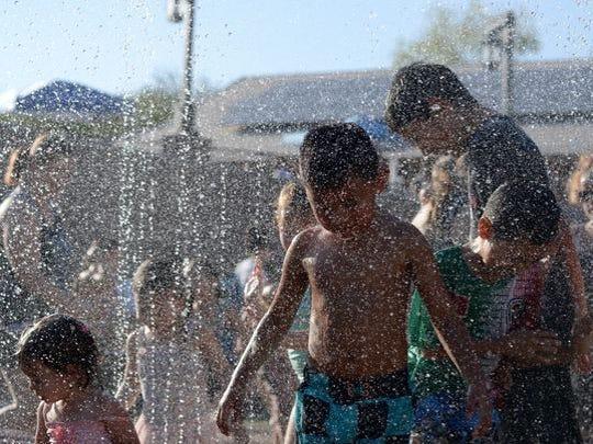 Los niños juegan en la plataforma de chapoteo en el Zoológico de Phoenix.