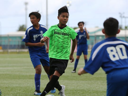 ASC Trust Islanders' E.J. Sablan looks to pass the ball around Guam Shipyard Wolverines defenders during an opening week U13 division match of the Aloha Maid Minetgot Cup Elite Youth League at the Guam Football Association National Training Center. The Islanders won 6-0.