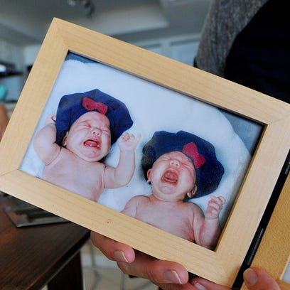 A photo of Olivia and Adrianna DeBoer as babies sits