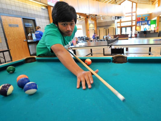 Keng Kue Khang, of Wausau, shoots some pool Thursday afternoon at the Boys & Girls Club of Wausau.
