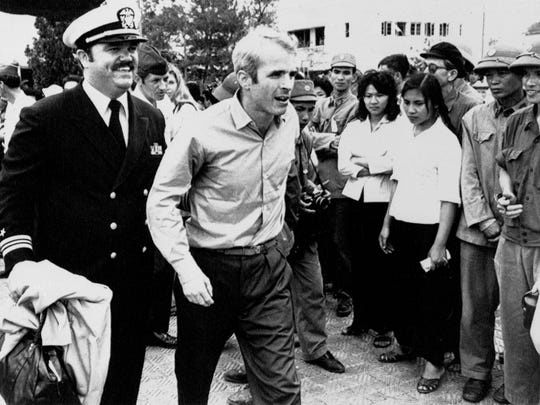 John McCain is escorted by Lt. Cmdr. Jay Coupe Jr., public relations officer, March 14, 1973, to Hanoi's Gia Lam Airport after the POW was released.