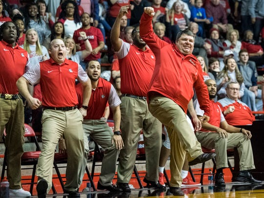 Bosse Head Coach Shane Burkhart (center) and the rest of the baseline show their excitement after netting a three-pointer during game one of the IHSAA Class 3A Regional Tournament against the Greensburg Pirates at Memorial Gym in Huntingburg, Ind., Saturday, March 10, 2018. The Bulldogs defeated the Pirates, 75-58, to advance to the evening's Regional Championship game.