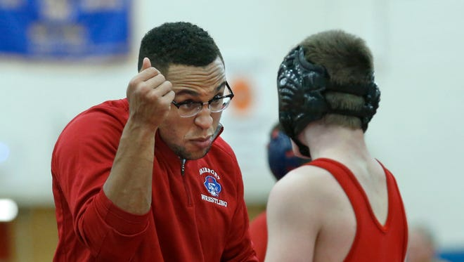 """Fairport coach John Martin Cannon talks to Patrick Unger during a dual meet versus Victor last season. Wrestlers in Business Western New York Chapter president Steve Sanko said that """"the sacrifice that coaches make for the kids is just tremendous."""""""