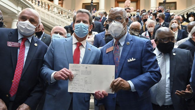 Gov. Brian Kemp, second from left, and Rep. Calvin Smyre hold the signed HB 426, hate-crimes legislation, on the last day of the legislative session at Georgia State Capitol in Atlanta, Friday, June 26, 2020. Kemp signed into law House Bill 426 which would impose additional penalties for crimes motivated by the victim's race, color, religion, national origin, sexual orientation, gender or disability.