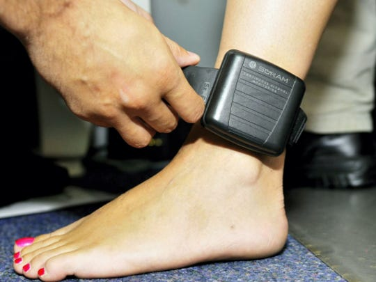 An electronic monitoring bracelet is seen on a woman's leg.