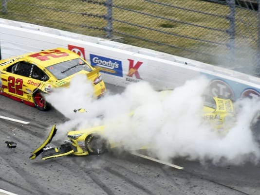 Joey Logano (22) and Matt Kenseth (20) tangle in Turn 1 during the NASCAR Sprint Cup Series auto race at Martinsville Speedway in Virginia on Sunday. Kenseth was suspended for two races for intentionally wrecking Logano.