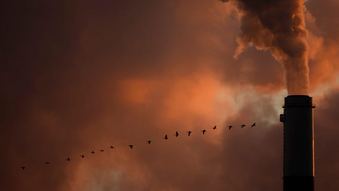 A flock of geese fly past a smokestack at the Jeffery Energy Center coal-burning power plant near Emmitt, Kan. Hundreds of corporations, insurance companies and pension funds are calling on world leaders to attack climate change by making it more costly for businesses to pollute.