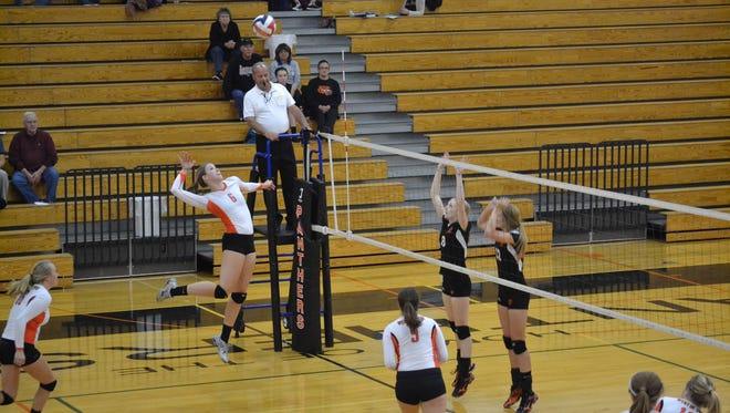 West De Pere's Heather Kocken goes up for a kill against Oconto Falls on Thursday night, Sept. 18. At right are Carolyn Malcheski (8) and Shelby Coron (12).