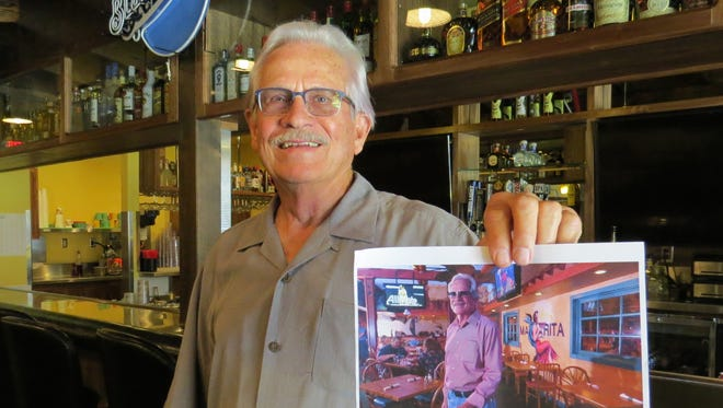 """We 100 percent gutted the inside, from the top of the roof to under the ground,"" Yolanda's Mexican Cafe co-founder Rod Geitzen says of the restaurant's remodeled location in Ventura. Here, he holds a Ventura County Star file photo while standing near the same spot where it was taken a year earlier."