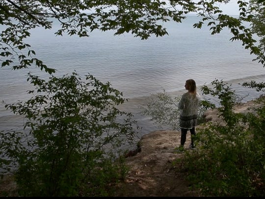 Lacey Sawyer looks over the sliver of high ground left at Durand Eastman Beach after high lake waters flooded area beaches.