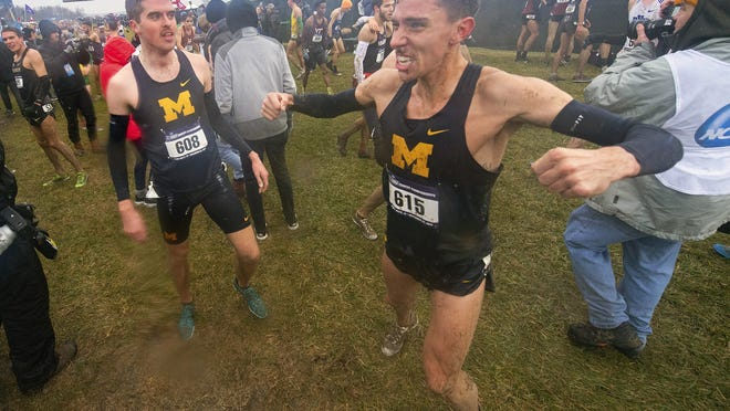 Michigan junior Devin Meyrer (615), right, reacts with teammate Jack Aho (608) after finishing the men's 2019 NCAA Division I Cross-Country Championship race, in Terre Haute, Ind. Athletes in sports other than football say they were not surprised to see the Big Ten and Pac-12 conferences postpone fall sports until the spring.