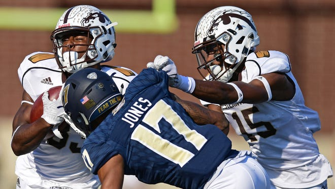 Western Michigan Michael Henry protects the ball while being tackled by Akron defensive back Bryce Jones (17) while being blocked by receiver Carrington Thompson in the first quarter on Oct. 15.
