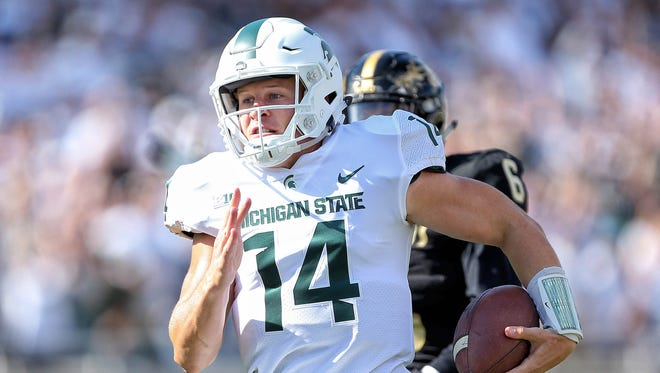 Michigan State Spartans quarterback Brian Lewerke (14) runs the ball for a touchdown during the first quarter of a game against the Western Michigan Broncos  at Spartan Stadium.