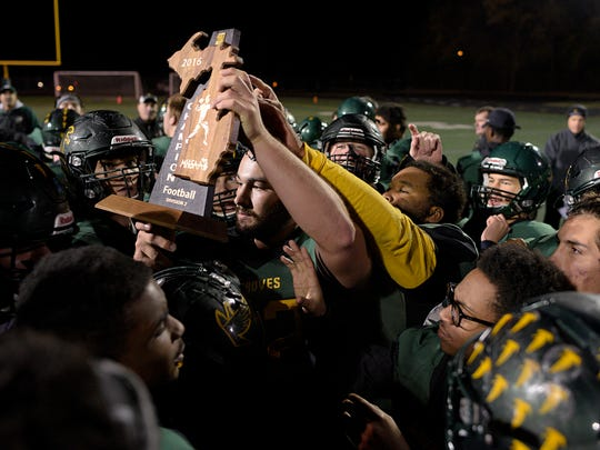 Groves players hold up the regional championship trophy Friday at Falcon Field after a convincing win over Grosse Pointe South.