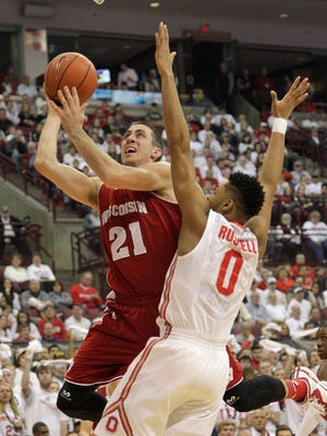 Wisconsin's Josh Gasser, left, shoots over Ohio State's D'Angelo Russell during the first half of an NCAA college basketball game Sunday in Columbus, Ohio.