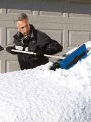 A man uses a Snow Joe snow broom with an ice scraper on the window shield of a car covered in snow.